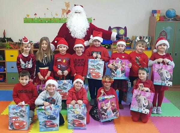 Dzieci z oddziału przedszkolnego prezentują swoje paczki, które otrzymały od Mikołaja