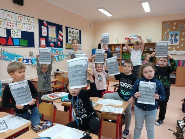 Uczniowie prezentują ulotki dotyczące bezpiecznego internetu