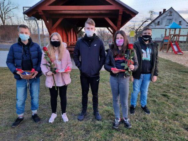 Uczniowie z kwiatami i czekoladkami wręczonymi z okazji Dnia Kobiet