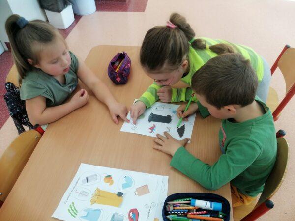 Dzieci podczas segregowania śmieci do odpowiednich pojemników