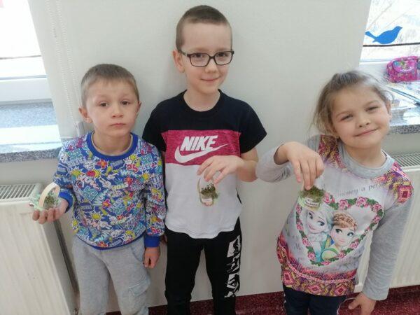 Oskar, Miłosz i Paulinka z koszyczkami z rzeżuchą
