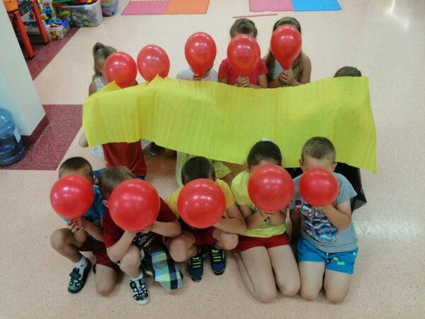 Dzieci z utworzoną flagą z balonów i bibuły