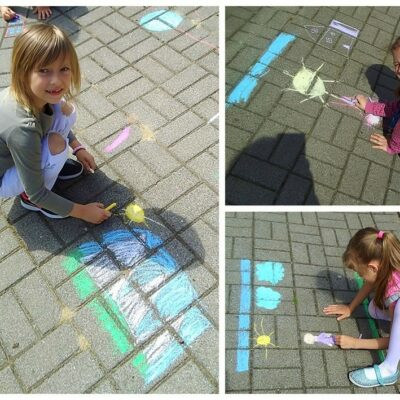 Uczennice rysują kredą na chodniku