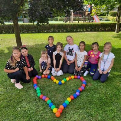 Uczniowie prezentują serce z kulek.