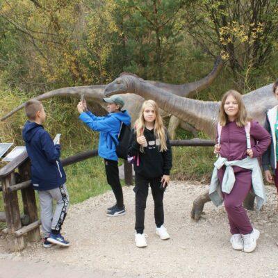 Uczniowie oglądają figury dinozaurów