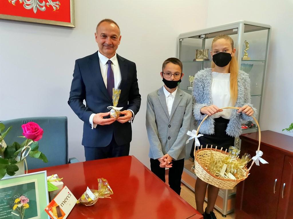 Przedstawiciele Samorządu Uczniowskiego wręczają babeczki nauczycielom